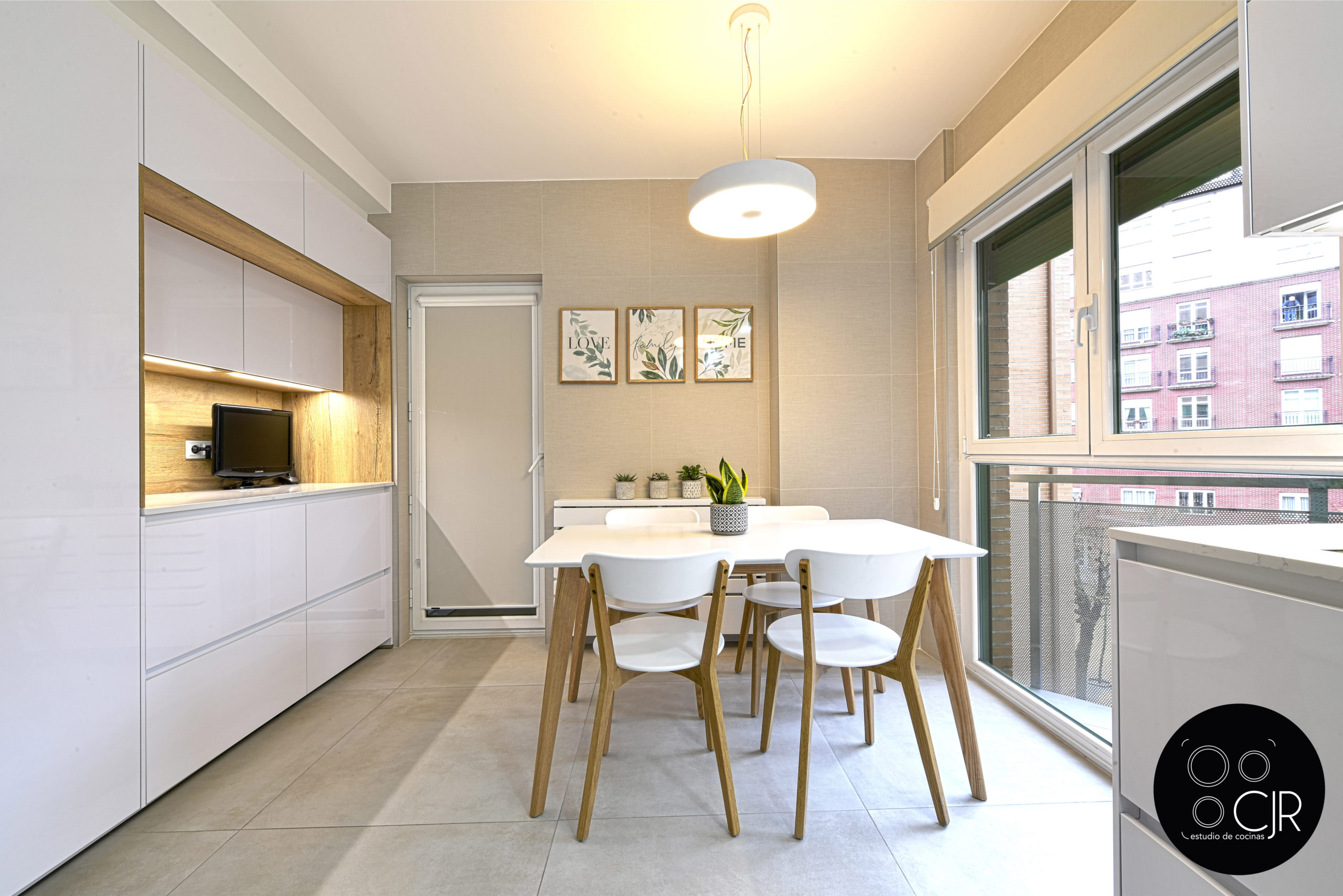 Zona de estar con mesa y sillas en cocina blanca y madera