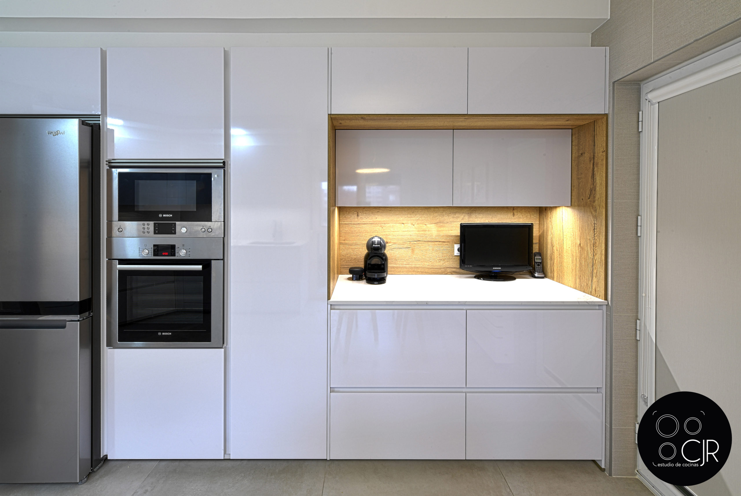 Vista frontal de cocina en blanco y madera con electrodomésticos