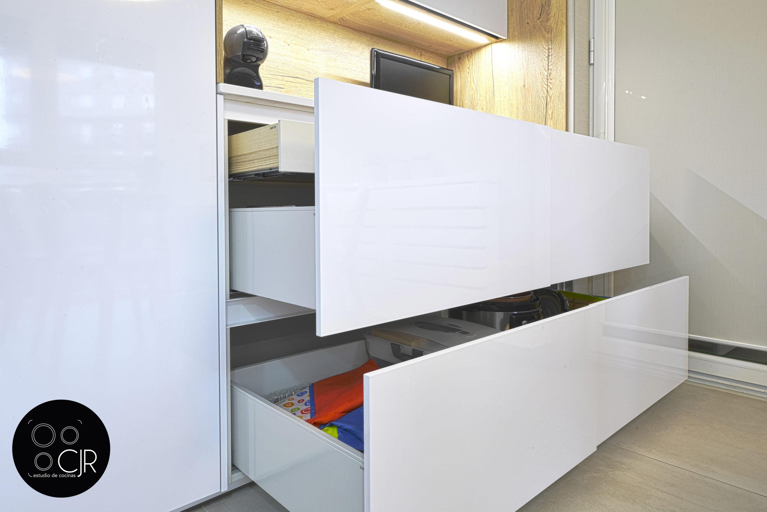 Cajones abiertos en cocina blanca y madera