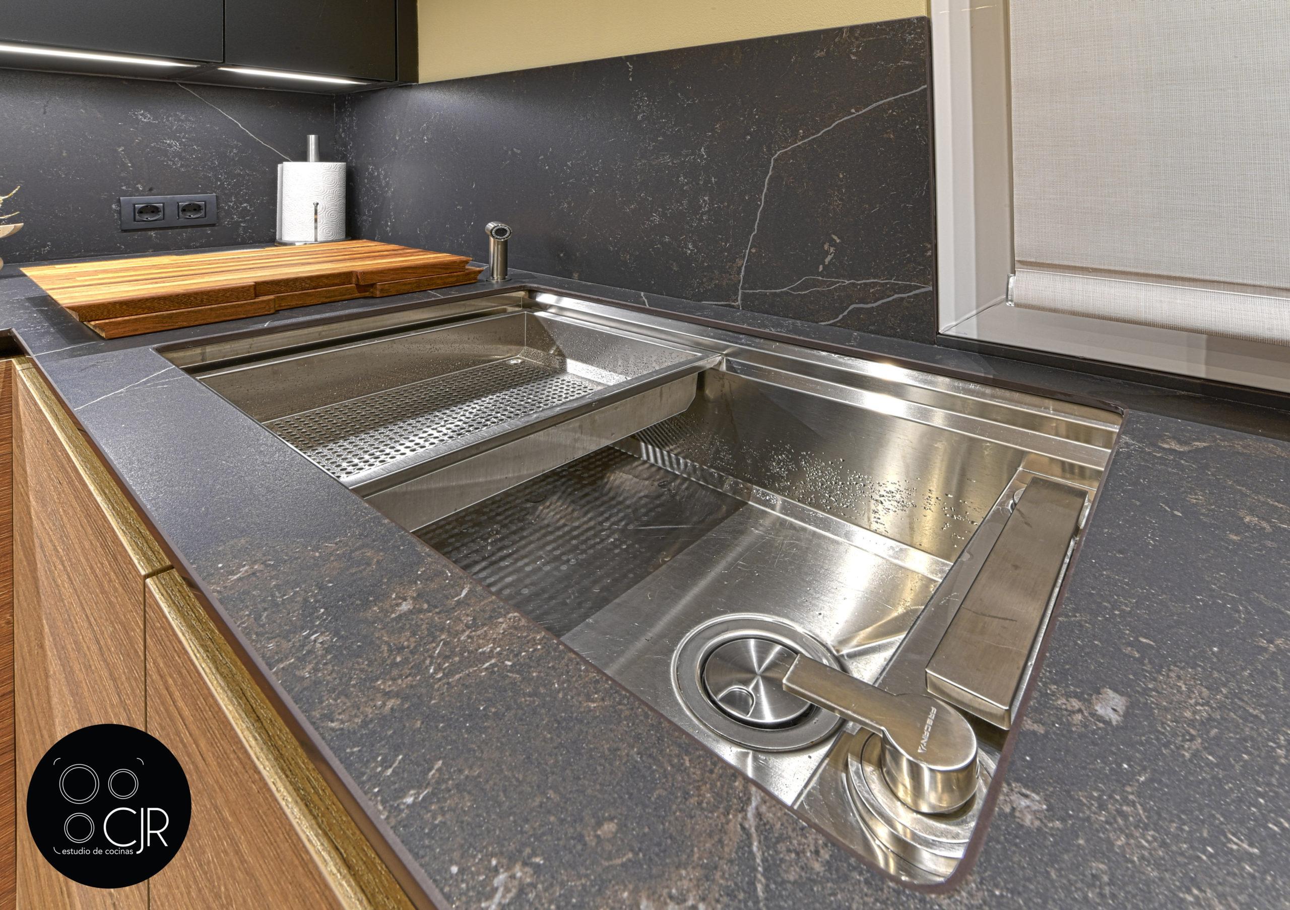 Fregadero recogido en cocina moderna negra y madera