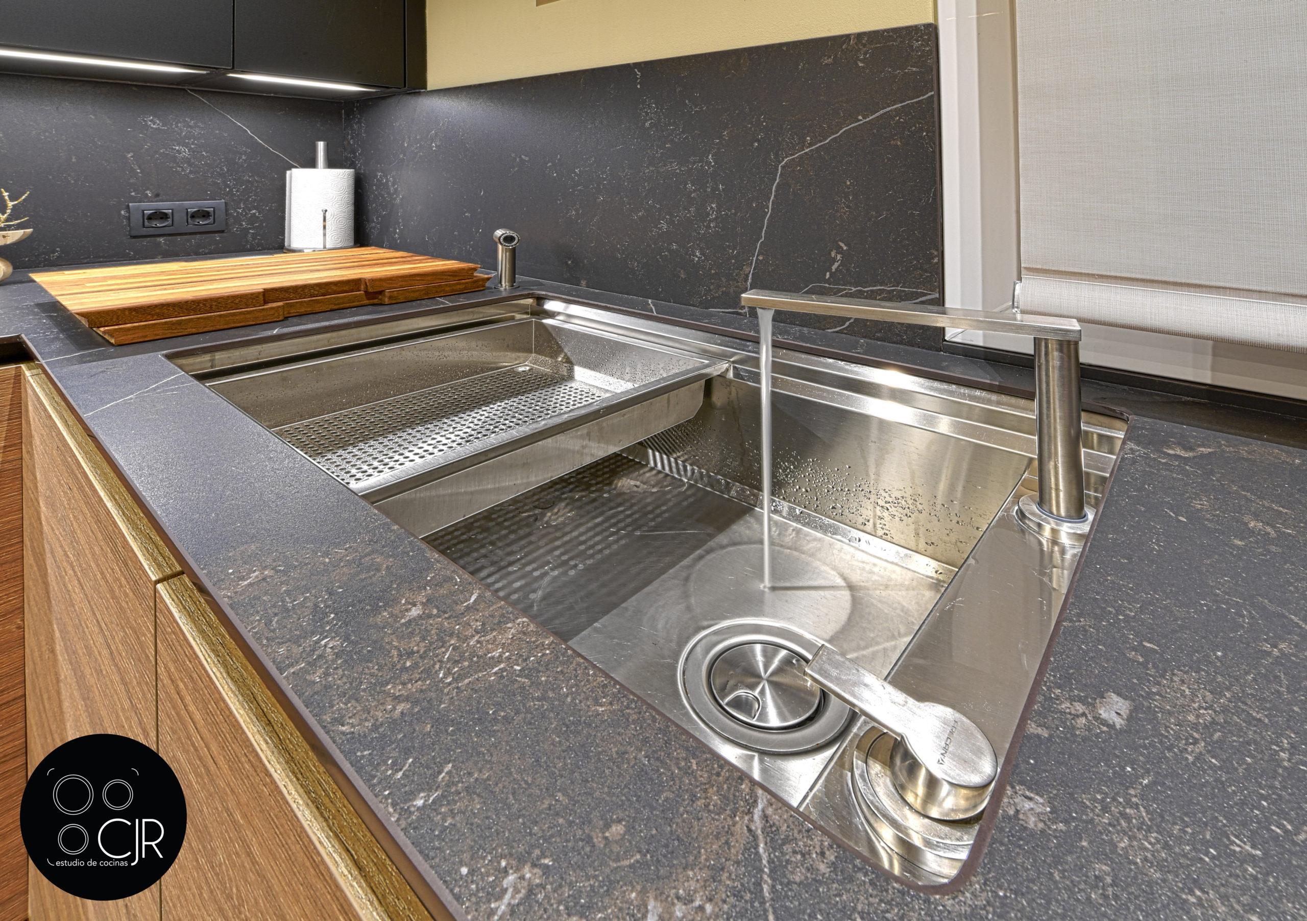 Fregadero con agua en la cocina moderna negra y madera