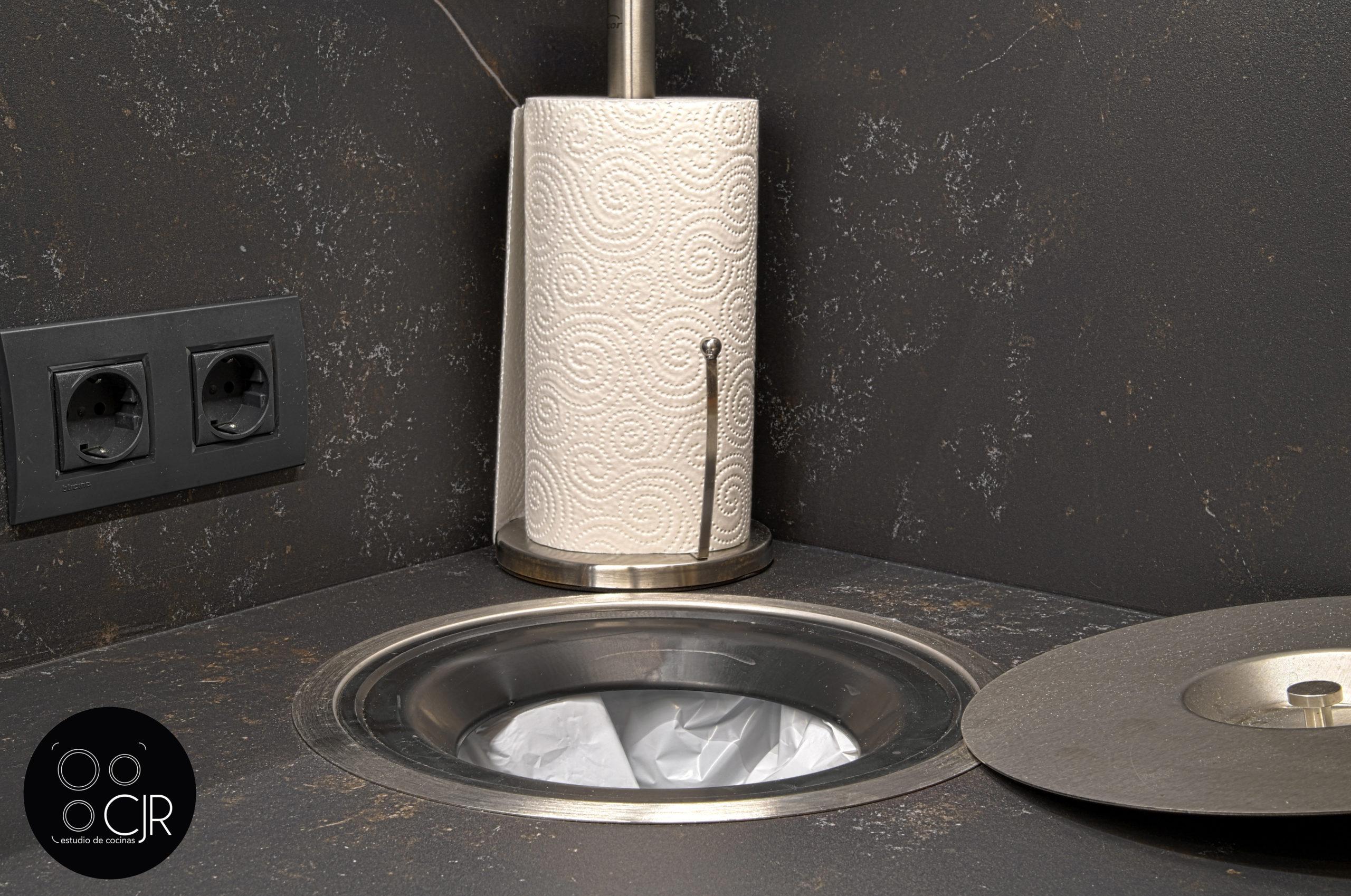 Zona de recogida de basura integrada con encimera en cocina moderna negra y madera