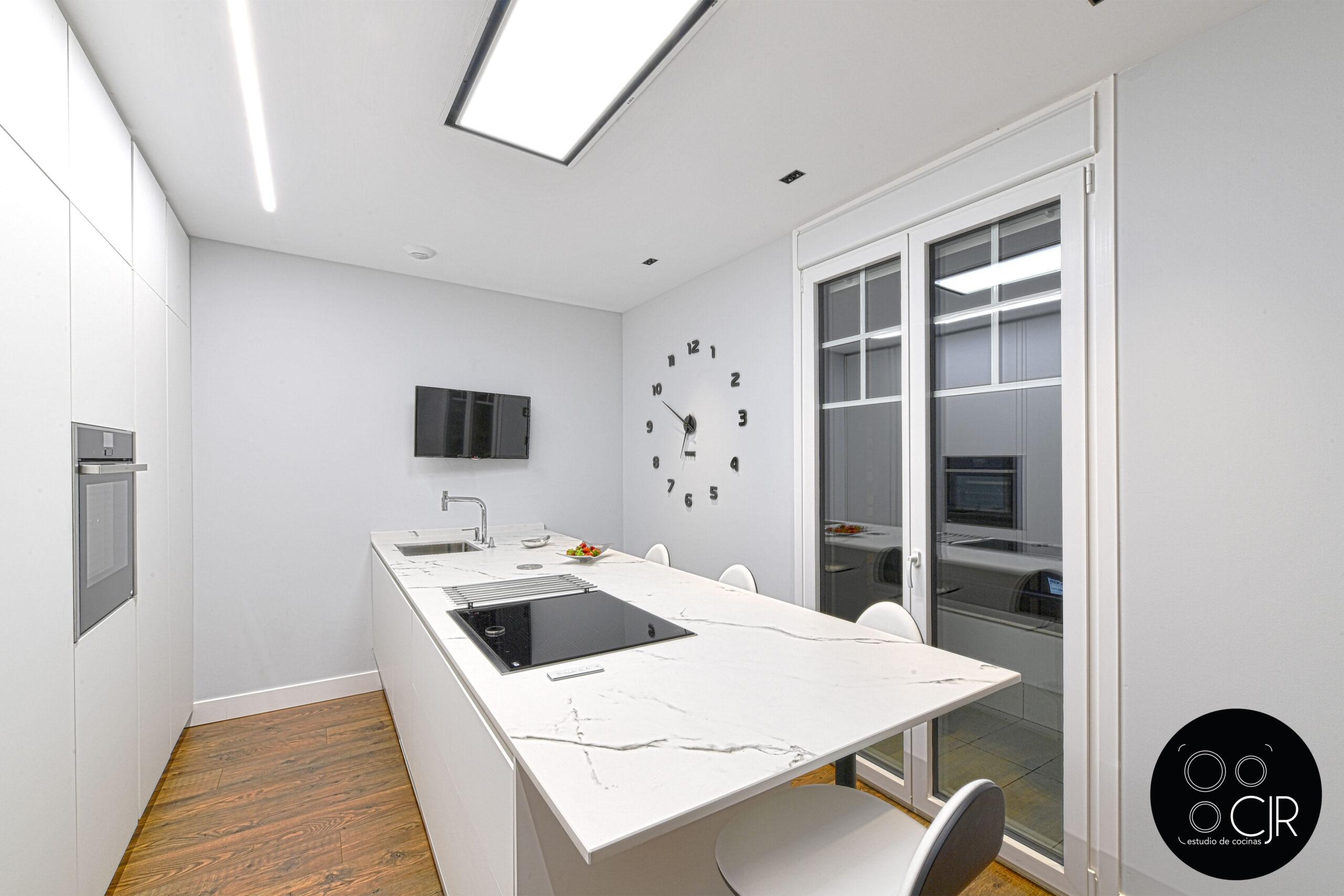 Vista de encimera y pared con ventana en cocina blanca mate sin tiradores