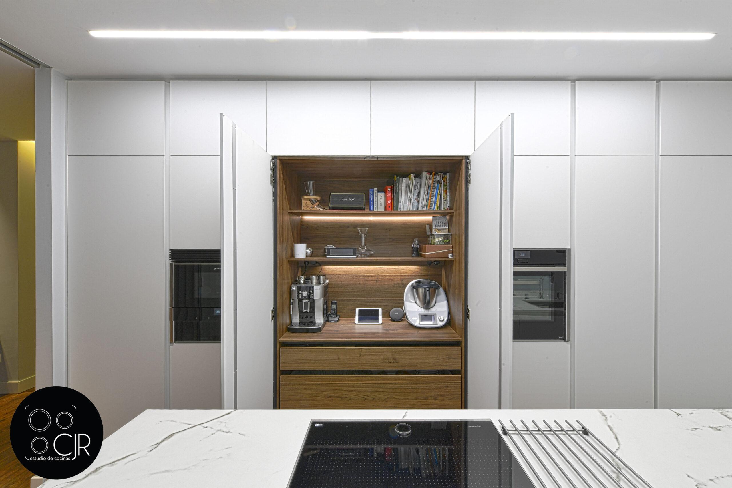 Puerta escamoteable en cocina blanca mate sin tiradores
