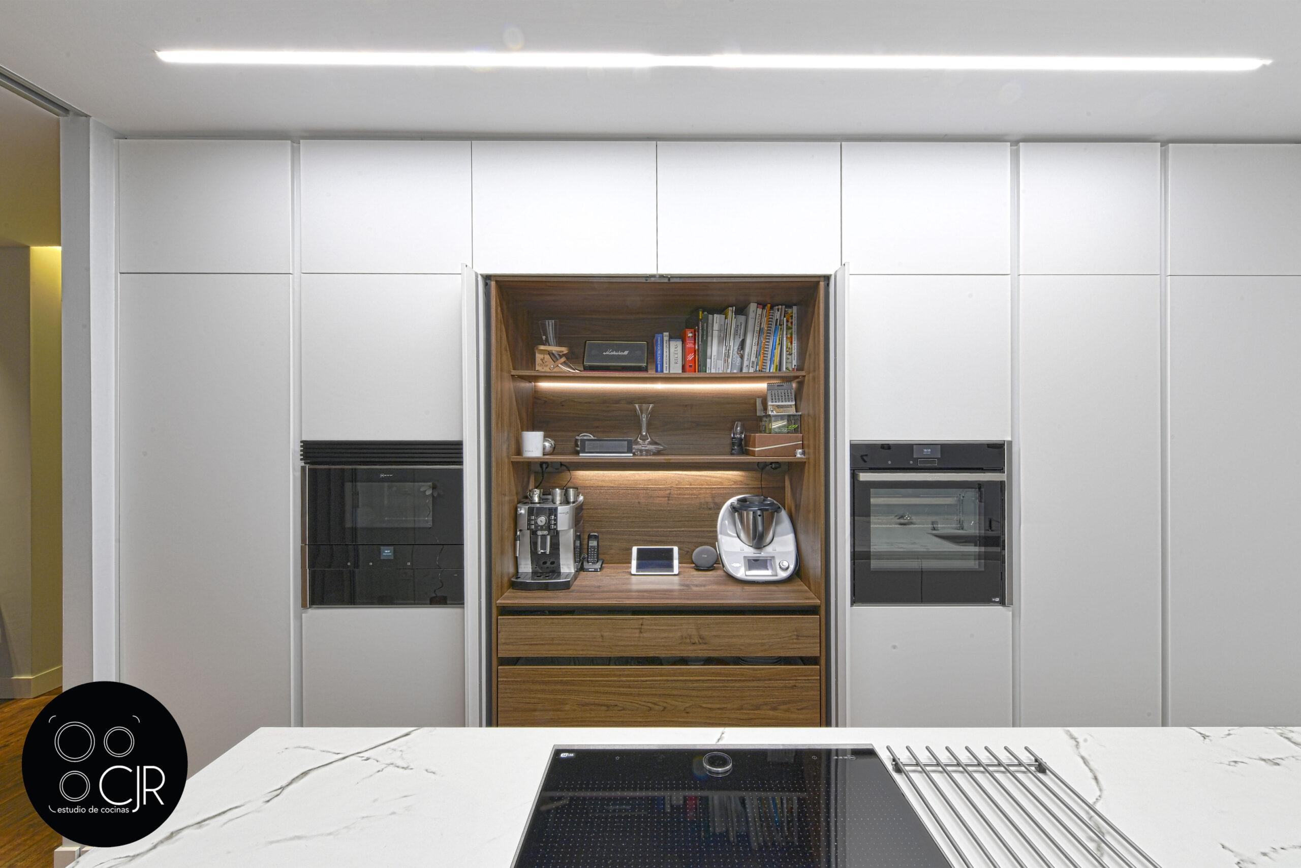 Puerta escamoteable recogida en la cocina blanca mate sin tiradores