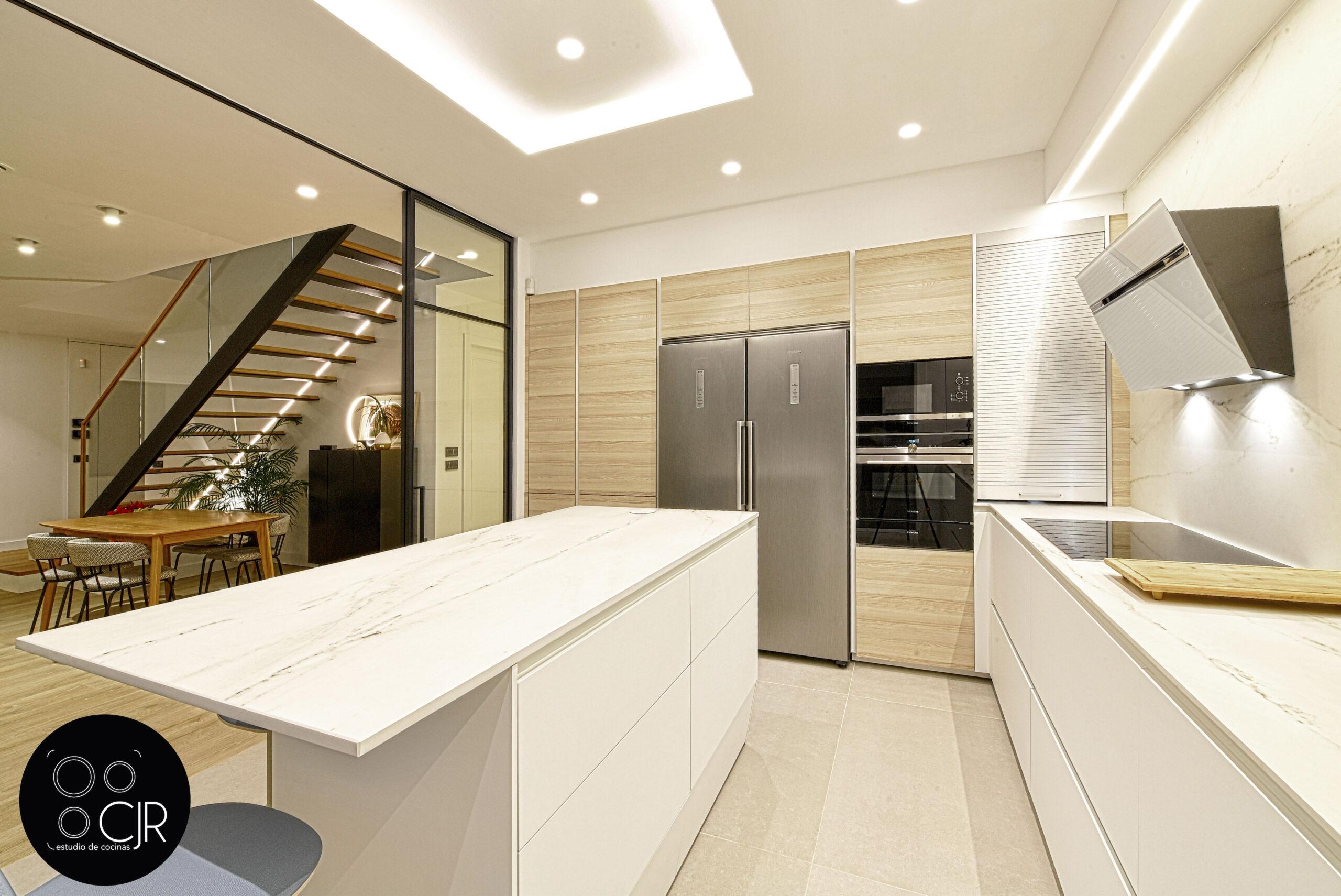 Cocina y parte del salón Cocina con isla blanca y madera