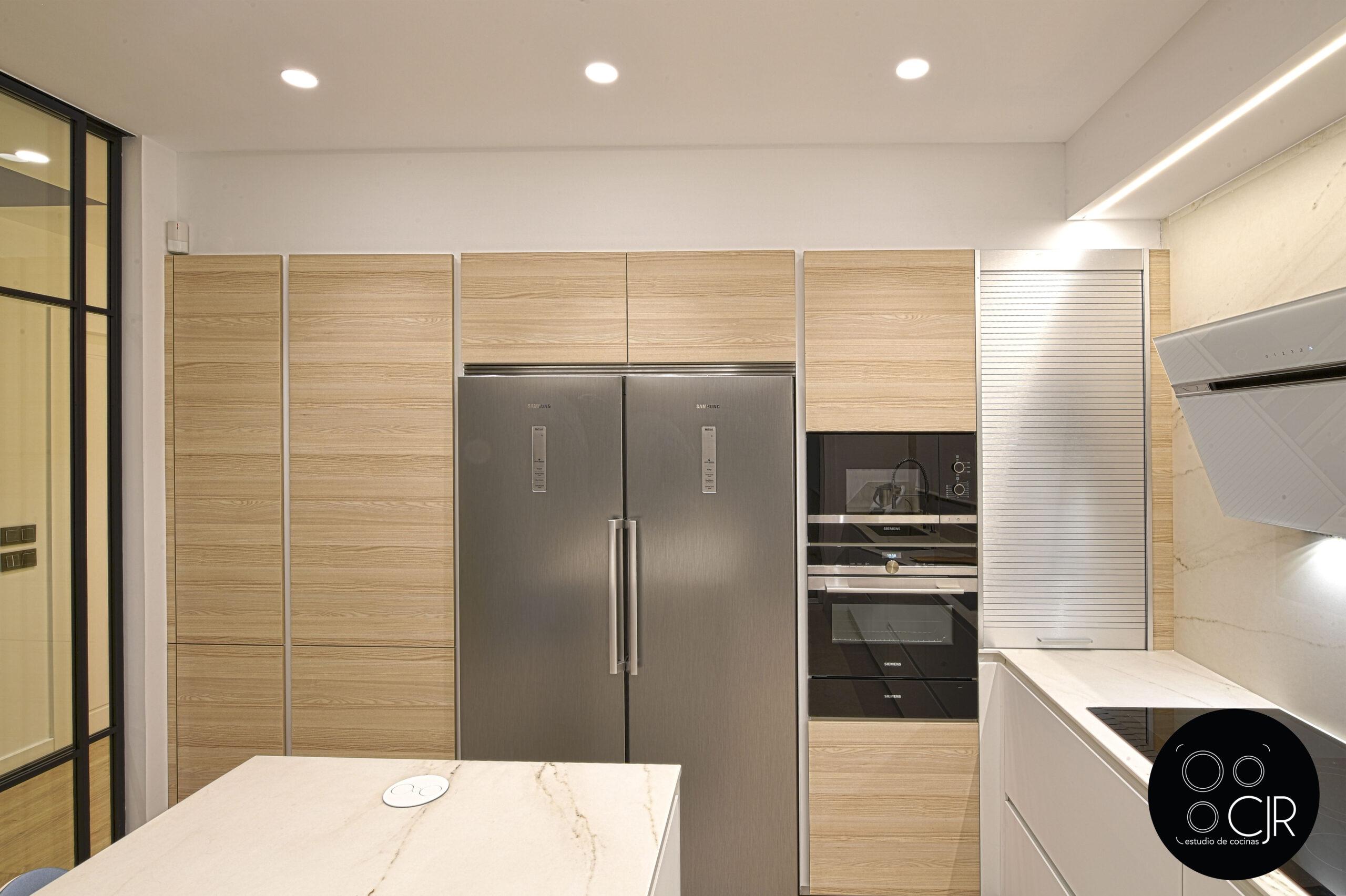 Zona electrodomésticos y muebles altos Cocina con isla blanca y madera