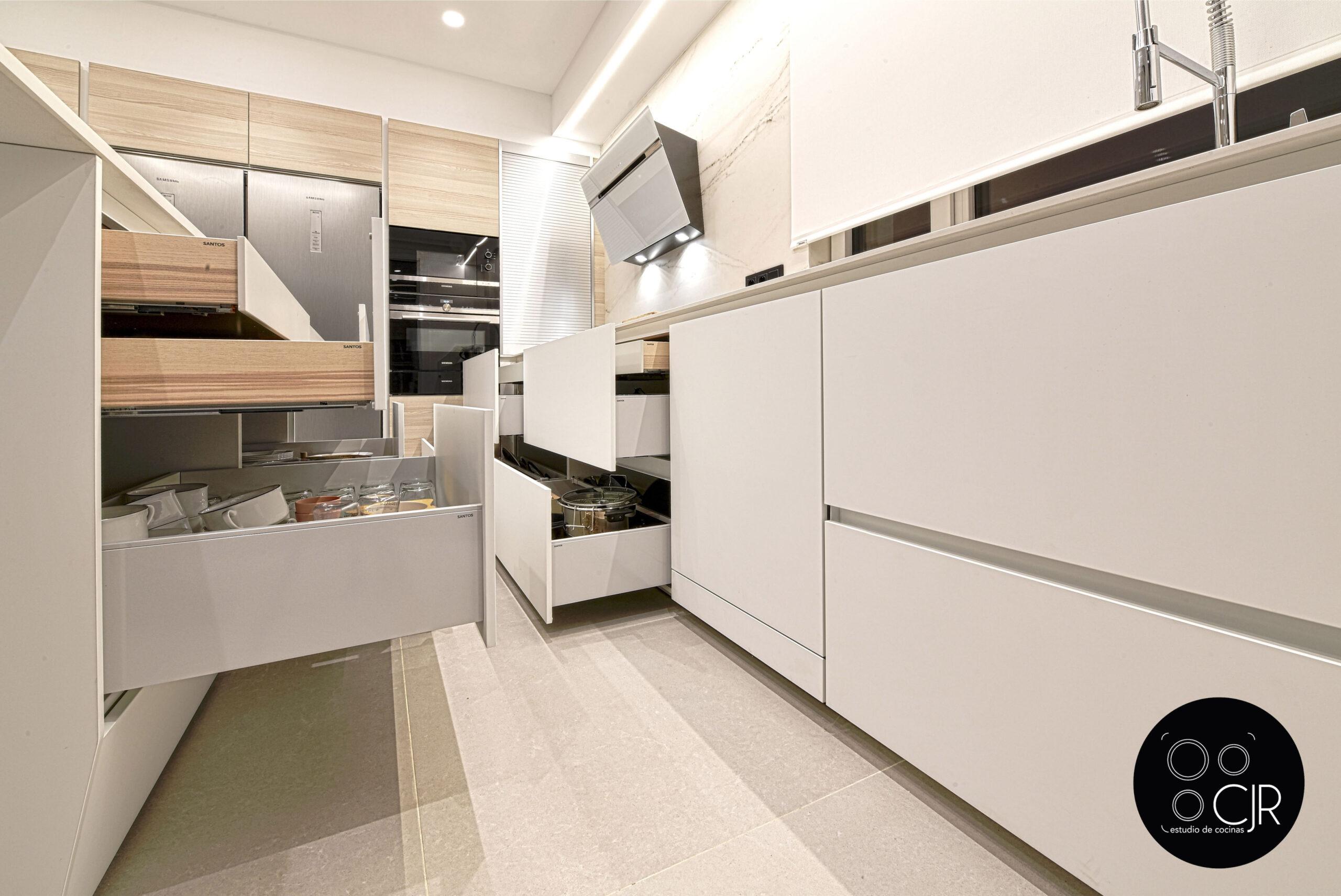 Otra vista de cajones abiertos Cocina con isla blanca y madera