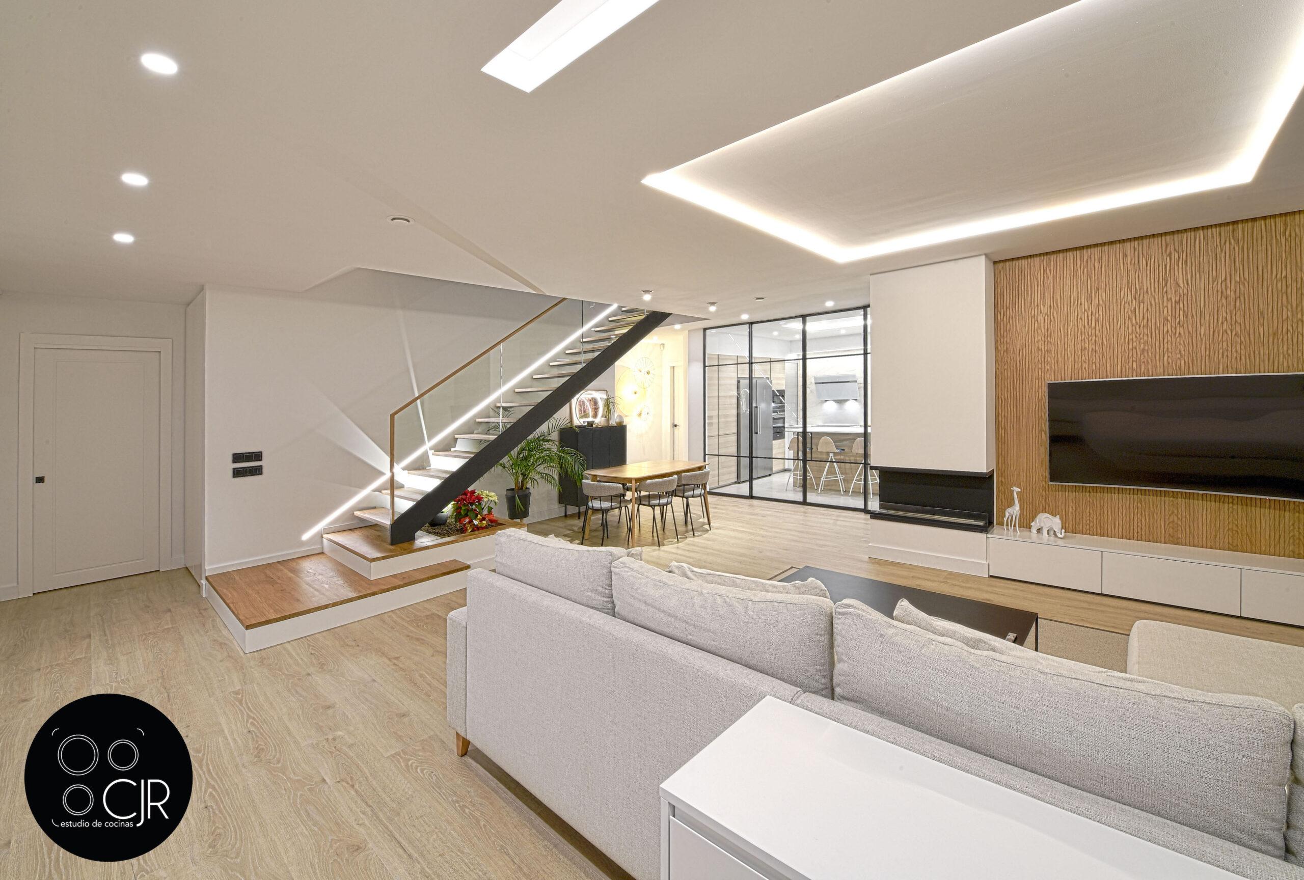 Vista salón y Cocina con isla blanca y madera