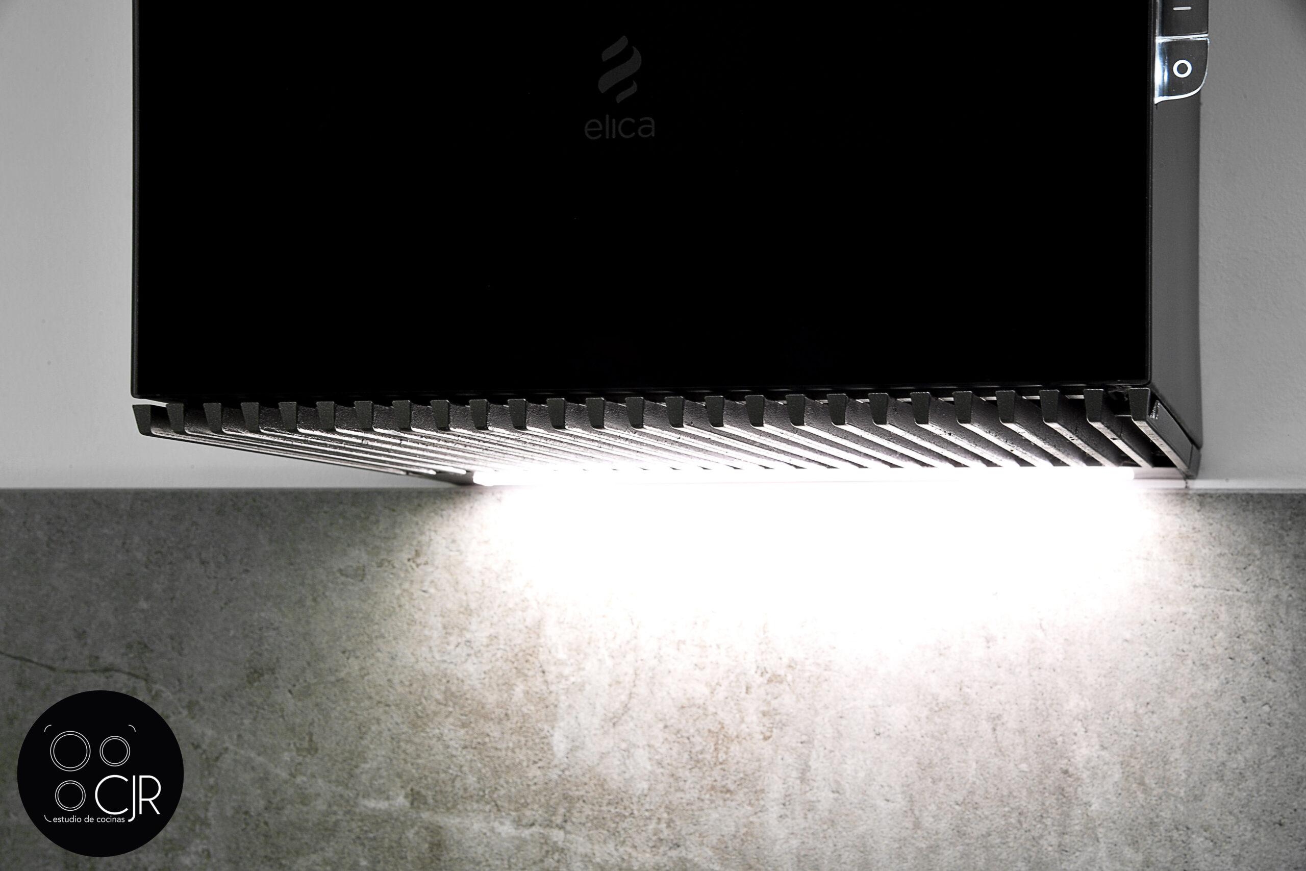 Campana elica desde cerca en la cocina blanca con encimera gris marengo