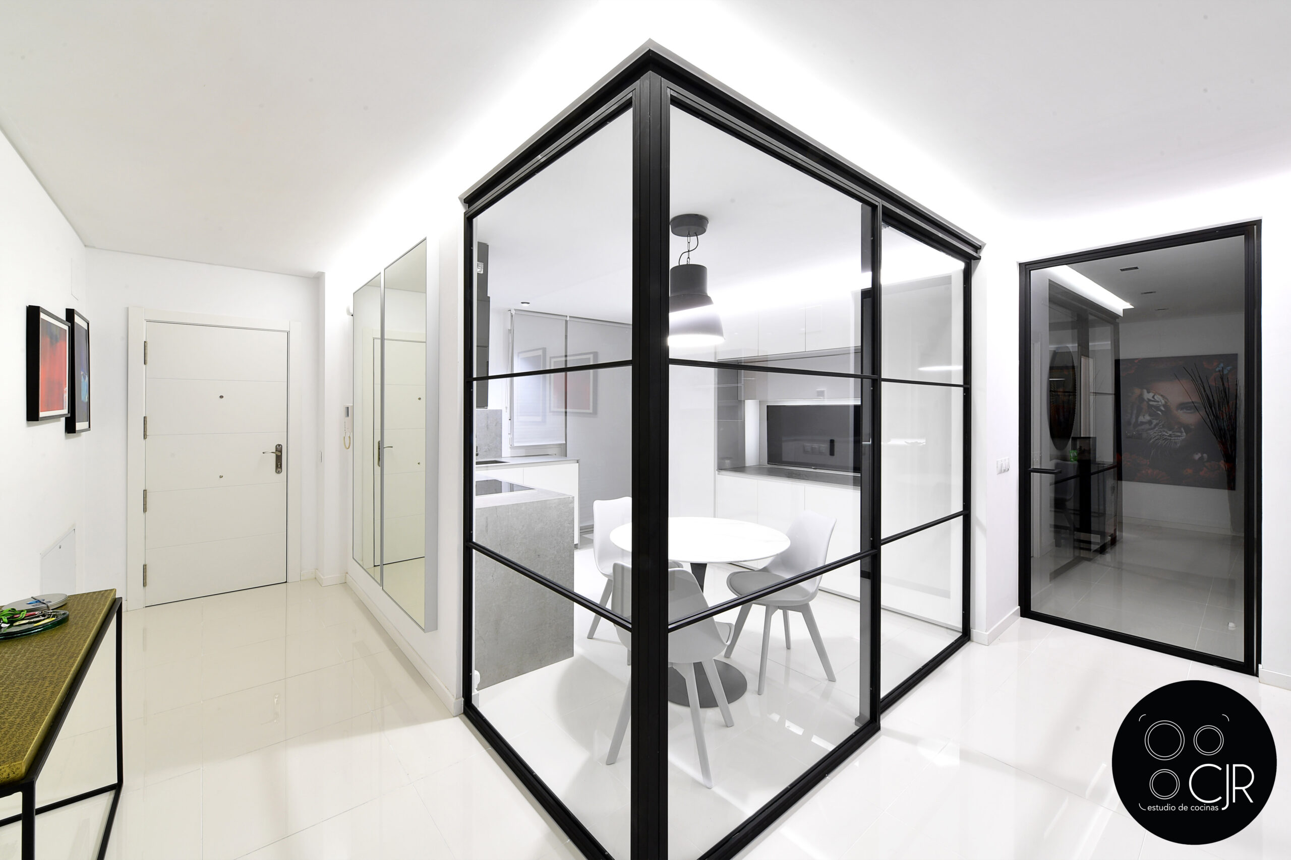 Cerramiento acristalado de la cocina blanca con encimera gris marengo