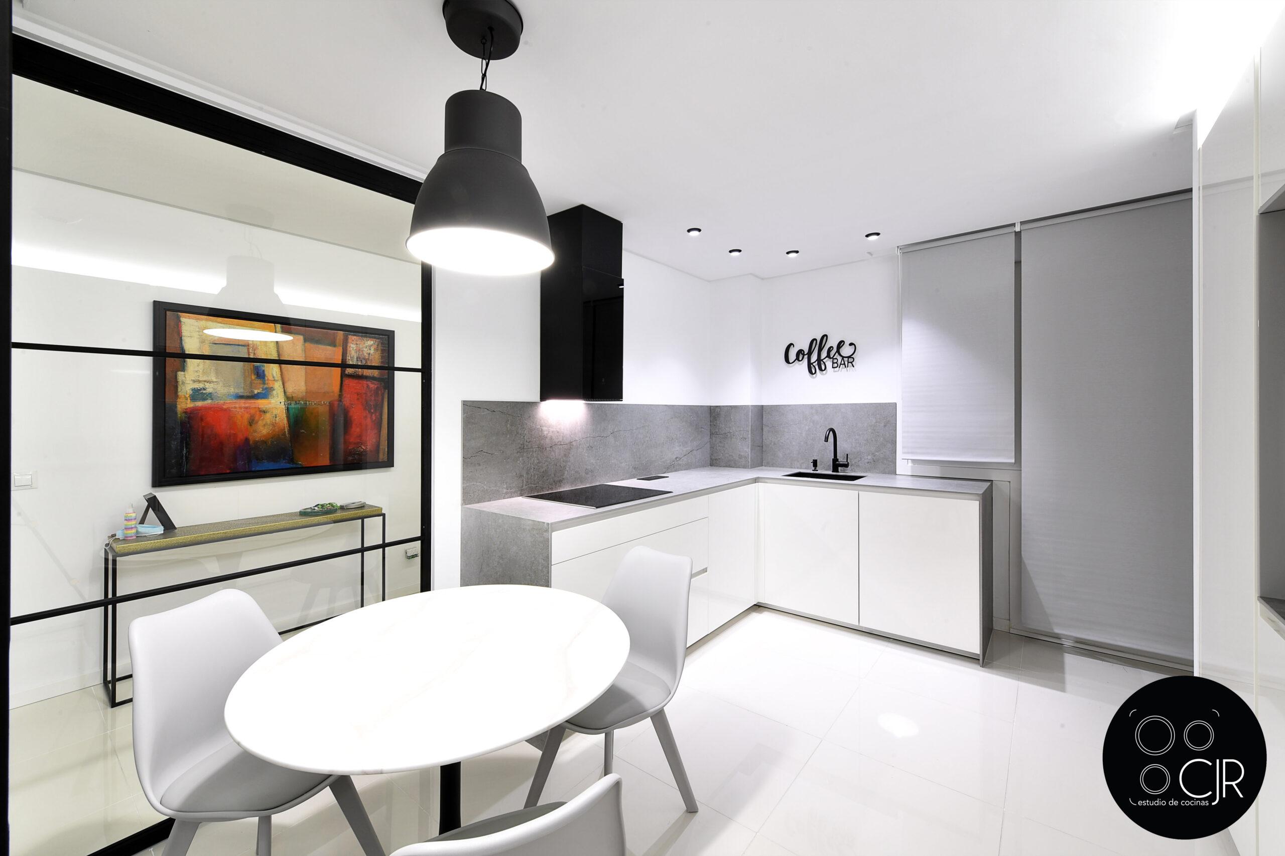 Vista desde una esquina de la cocina blanca con encimera gris marengo