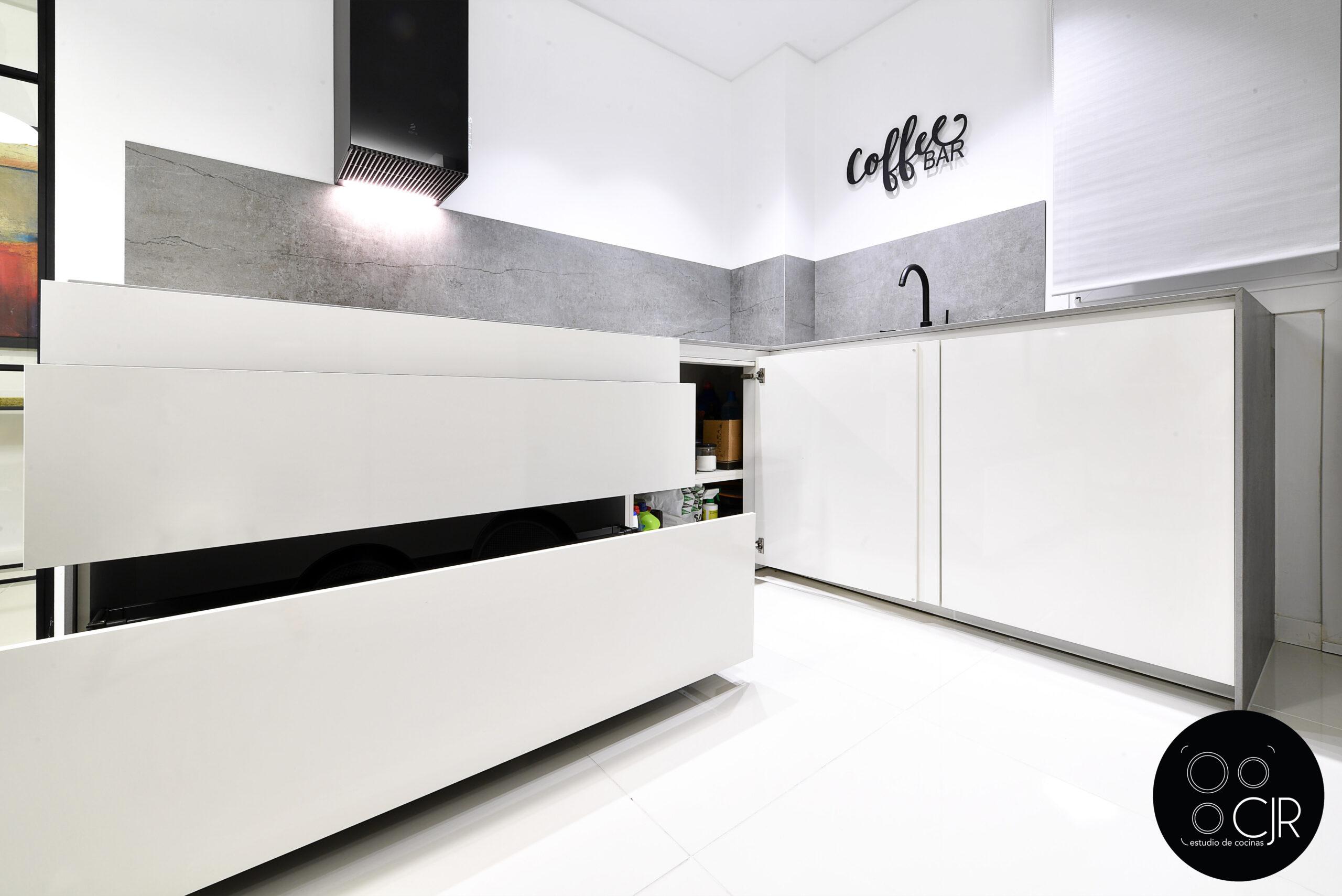 Cajones inferiores abiertos en la cocina blanca con encimera gris marengo